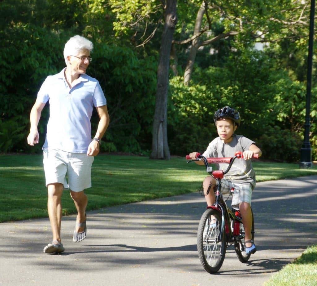 Man teaches kid to ride bike