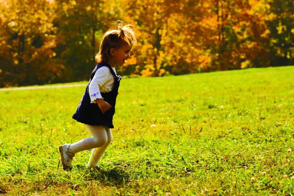 Little girl running on a field