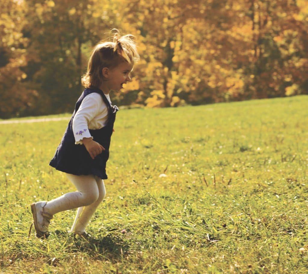 Little girl running on the grass field